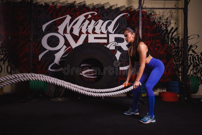 Die athletische Frau, die etwas crossfit tut, trainiert mit einem schweren Seil stockfotografie