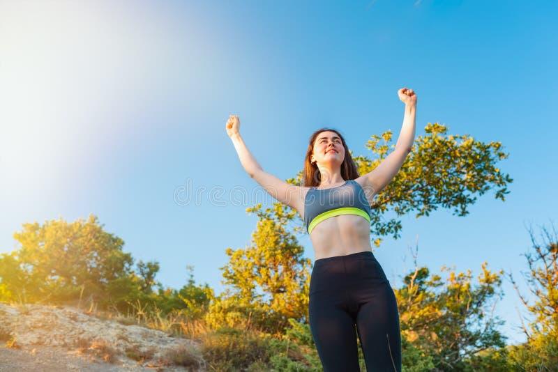 Die athletische junge Frau hob ihre Hände zum Himmel an und freute sich am Sieg Das Konzept des Sports, gesunder Lebensstil exemp lizenzfreies stockbild
