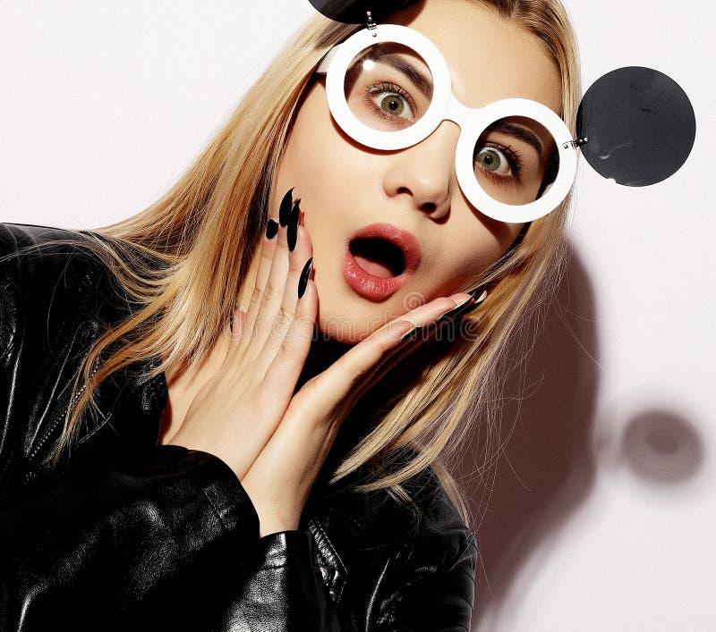 Die attraktive überraschte junge Frau, die kreative Sonnenbrille trägt, ist lizenzfreie stockbilder