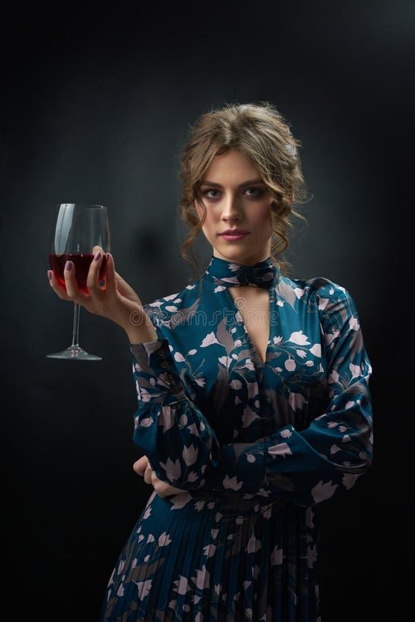 Die attraktive Frau, die blaues Kleid trägt, hält Weinglas stockfotografie
