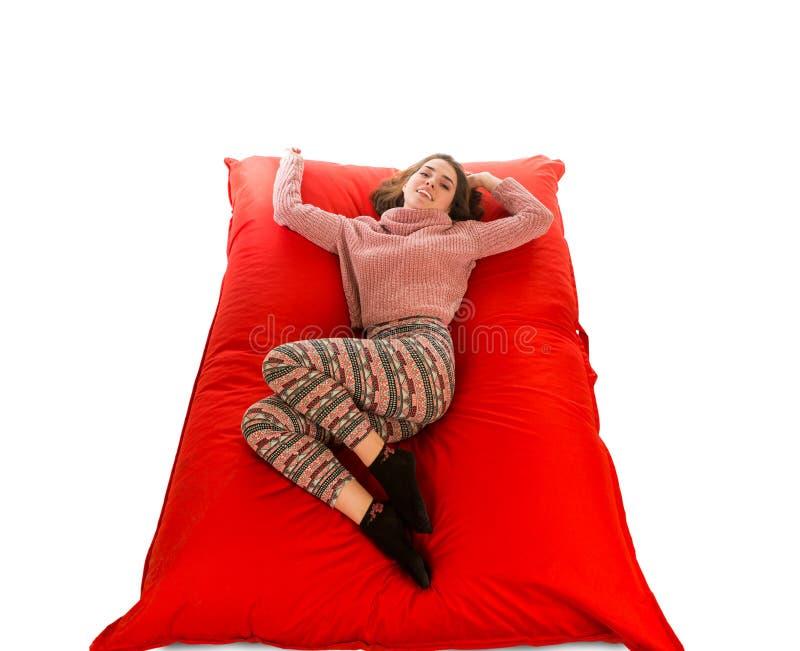 Die attraktive Frau, die auf rotem Quadrat liegt, formte Sitzsacksofaisolat stockfotos