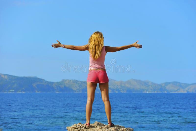 Die attraktive Frau, die mit den Armen steht, öffnen sich zur Luft, die vor dem Meer frei ist lizenzfreie stockfotos