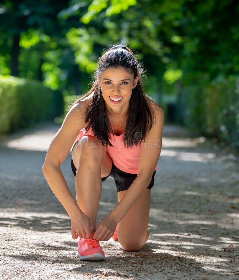 Die attraktive lateinische Sportläuferfrau, die ihren Schuhturnschuh bindet, schnürt sich im Park stockbilder