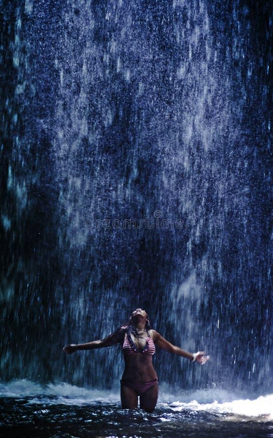 Die attraktive und sexy Asiatin, die glücklich und frei sich fühlt, machte unter schöner Wasserfallnaturlandschaft in Tourismus S stockbild