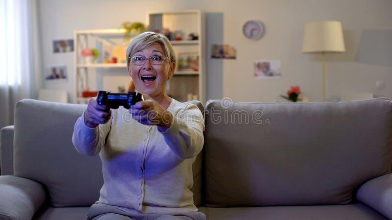 Die aufgeregte alte Frau, die Videospiel auf Steuerknüppel, freuenden Sieg spielt, unterhalten lizenzfreie stockfotos