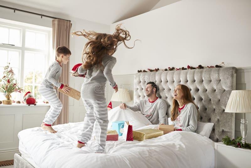 Die aufgeregten Kinder, die auf Eltern springen, gehen zu Hause als Familien-offene Geschenke am Weihnachtstag zu Bett stockfotos