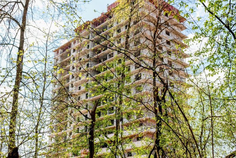 Die Aufrichtung eines Hochhausmultiwohnungsgebäudes im Wald stockbild