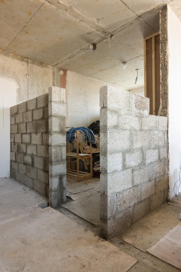 Die Aufrichtung von neuen Wänden von erweiterten Lehmblöcken in einem Neubau lizenzfreie stockbilder