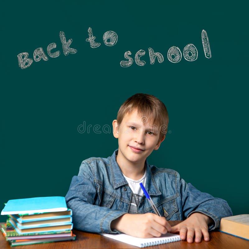 Die Aufschrift auf dem Brett ZURÜCK ZU SCHULE Ein Junge des europäischen Auftrittes sitzt auf dem Hintergrund des Schulgrünbrette lizenzfreies stockbild
