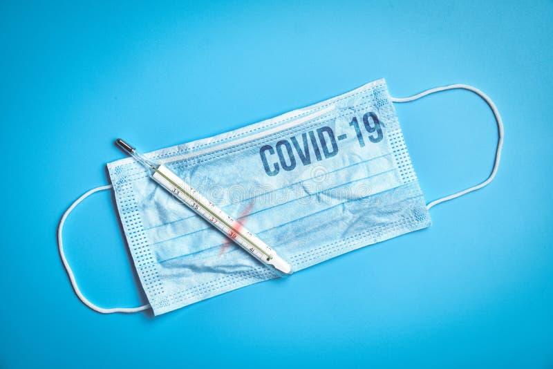 Die Aufschrift auf der Schutzmaske ist das Coronavirus COVID-19 neben dem Thermometer mit 39 Temperatur auf blauer Farbe lizenzfreies stockfoto
