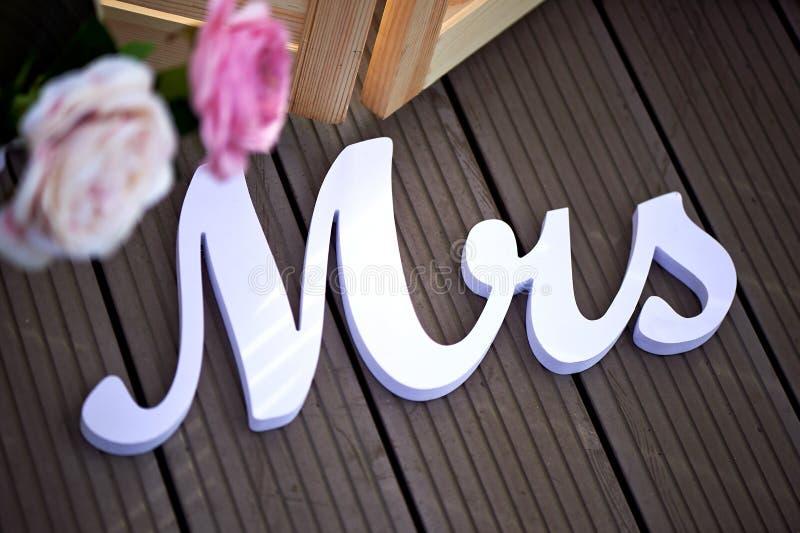 Die Aufschrift Frau als Dekor an der Hochzeit gegen die Dunkelheit verschalt mit rosa Blumen lizenzfreie stockfotos