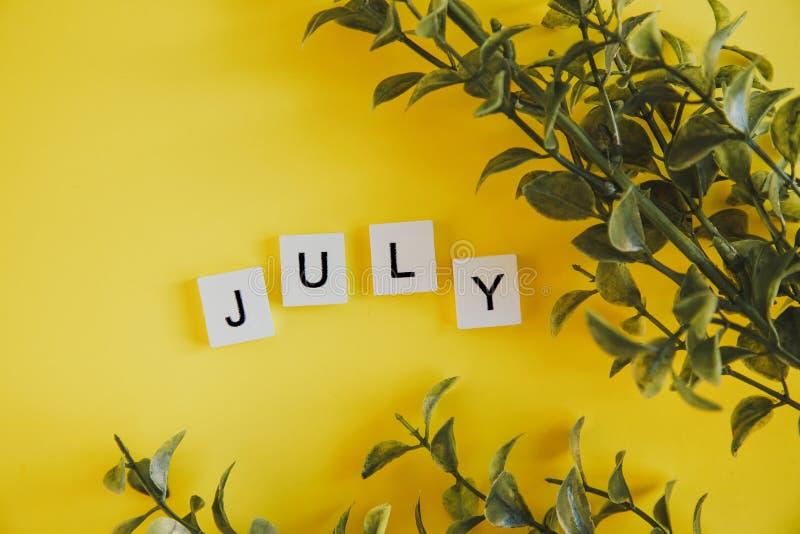 Die Aufschrift Juli auf den Buchstaben der Tastatur auf einem gelben Hintergrund mit Niederlassungsblumen lizenzfreies stockbild