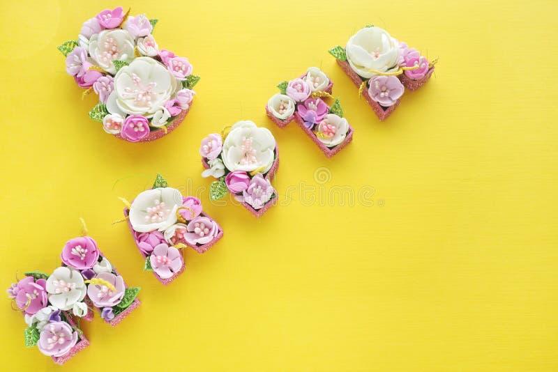 Die Aufschrift am 8. März wird mit mehrfarbigen Blumen in den russischen Buchstaben auf einem hellen gelben Hintergrund gezeichne stockfotografie