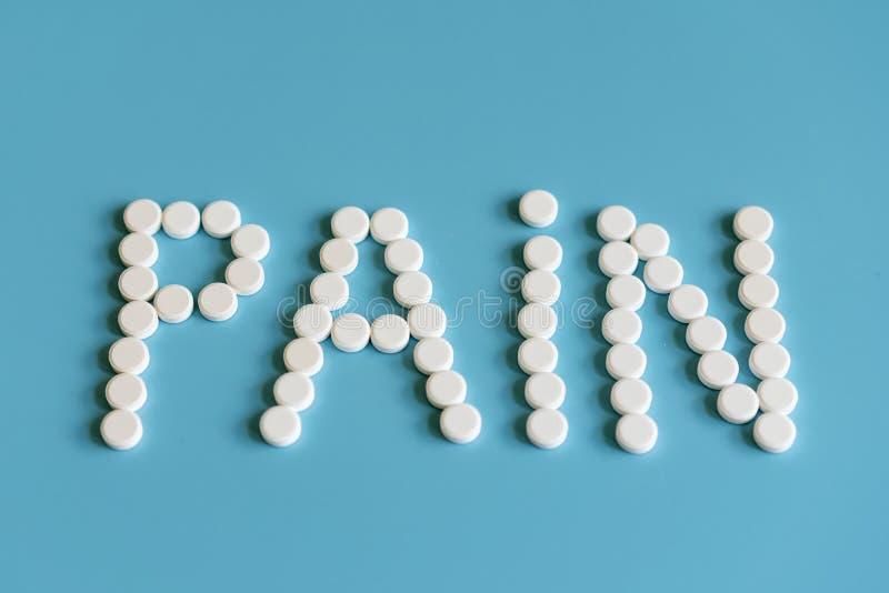 Die Aufschrift von Schmerz wird mit weißen Pillen auf einem blauen Hintergrund ausgebreitet Schmerz-Steuerung - Tablets stockbilder