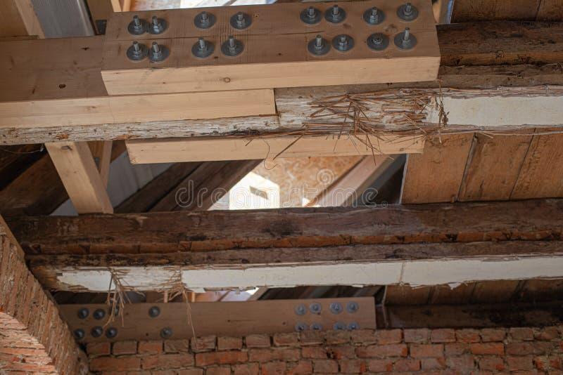 Die aufwändige Arbeit eines alten Hauses wird wiederhergestellt, wobei alte Balken durch neue verstärkt werden stockbild