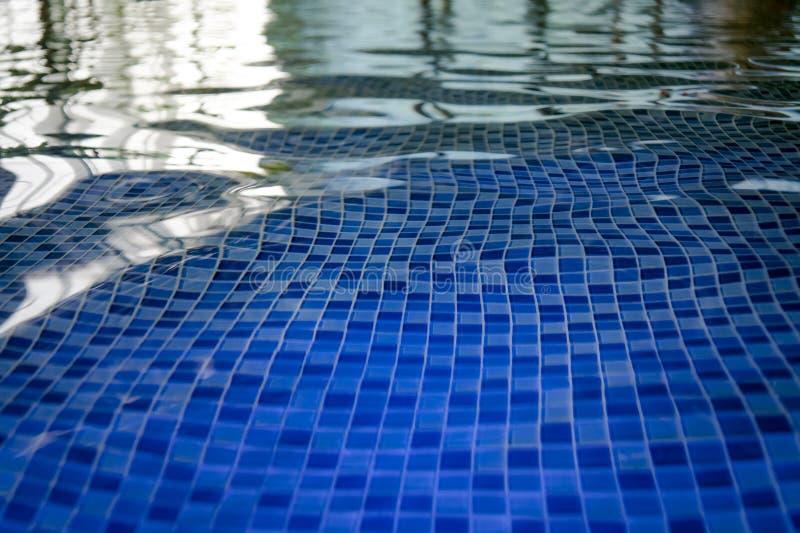 Die azur Mosaikunterseite eines aquapark Pools Eine Ansicht zum Fliesenboden durch das Trinkwasser des Hallenbads Kräuselungen un stockfotografie