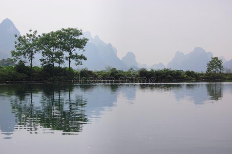 Die Bäume durch den Fluss lizenzfreie stockfotos