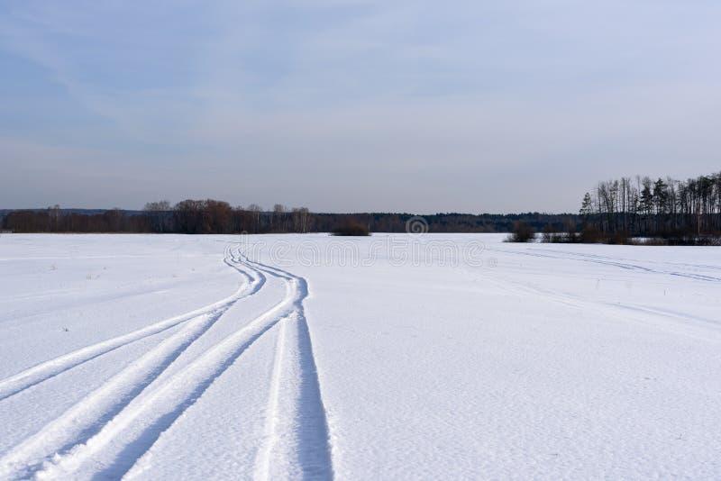 Die Bahn auf einem schneebedeckten Feld, das fern verlässt stockfoto