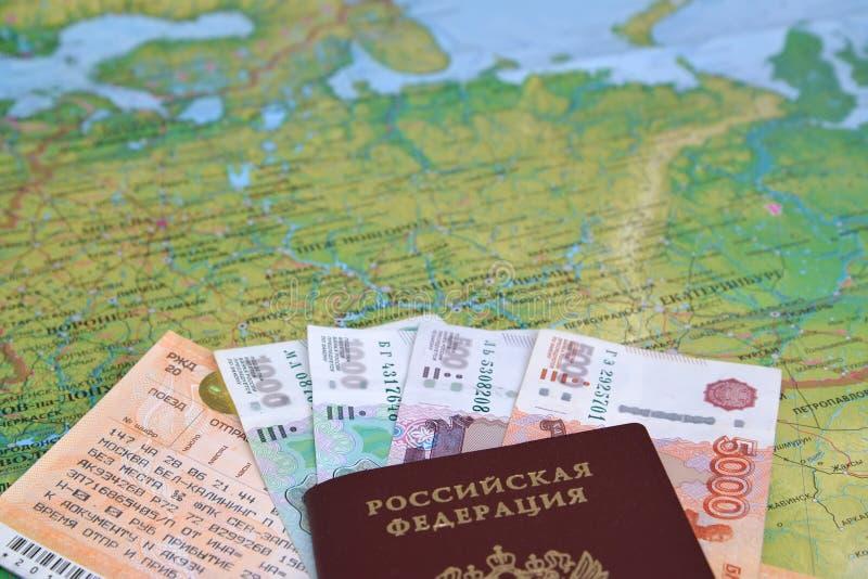 Die Bahnfahrkarte, das Geld und der russische Pass liegen auf einer Karte von Russland stockfotografie
