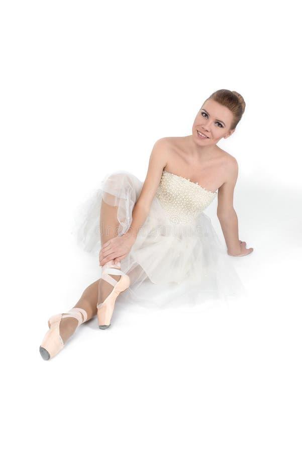 Die Ballerina in den pointes und in einem Kleid sitzt auf einem weißen backg lizenzfreie stockbilder