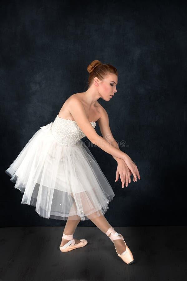 Die Ballerina in den pointes und in einem Kleid tanzt auf ein dunkles backgroun lizenzfreies stockbild