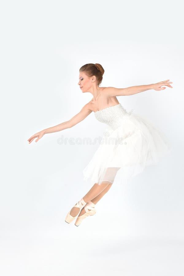 Die Ballerina in den pointes und in einem Kleid tanzt auf ein weißes backgroun lizenzfreies stockbild