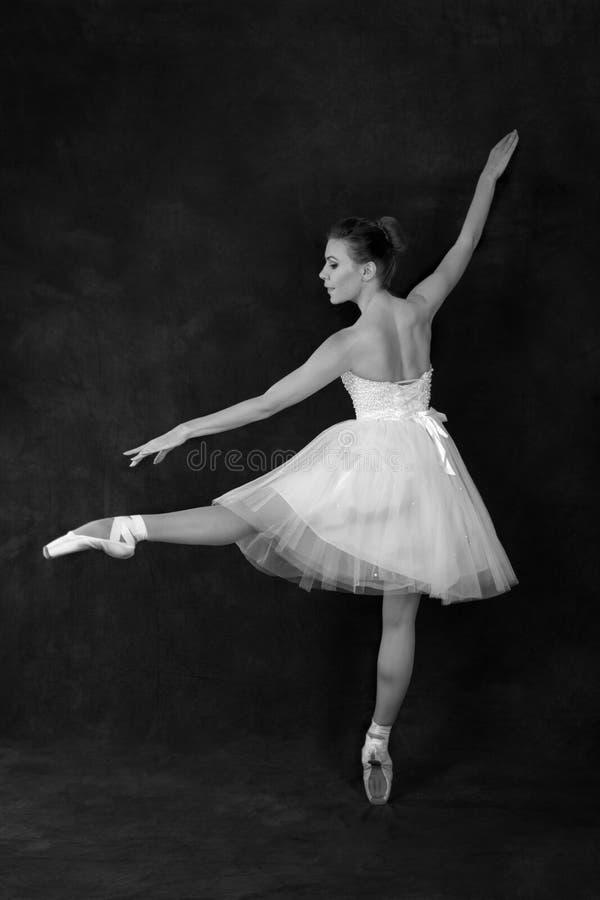 Die Ballerina in den pointes und in einem Kleid tanzt auf ein weißes backgroun lizenzfreies stockfoto