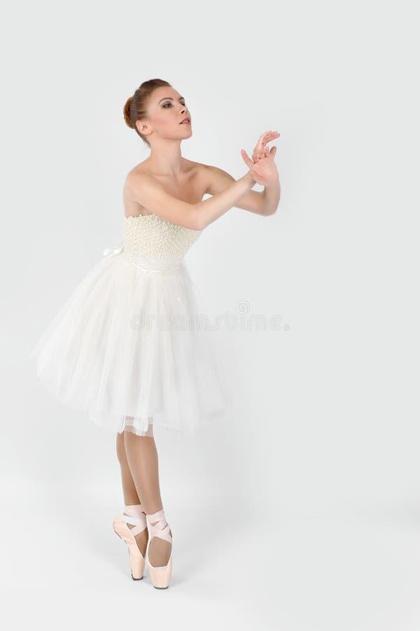 Die Ballerina in den pointes und in einem weißen Kleid tanzt auf ein weißes Ba stockfotografie