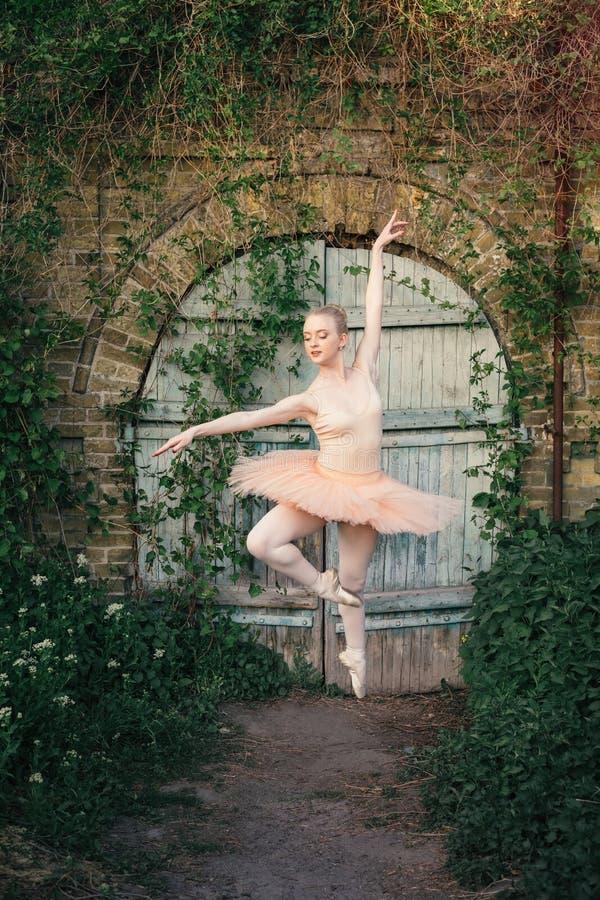 Die Ballerina, die draußen klassisches Ballett tanzt, wirft im städtischen backgro auf lizenzfreies stockbild