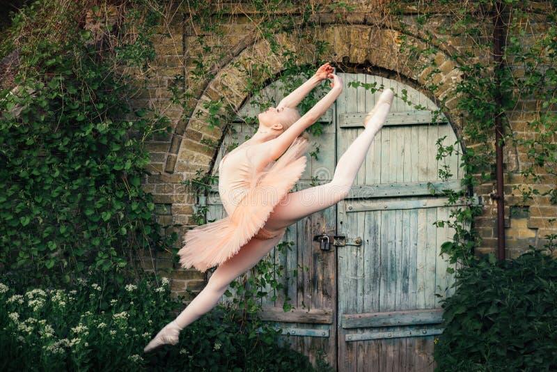 Die Ballerina, die draußen klassisches Ballett tanzt, wirft im städtischen backgro auf lizenzfreie stockfotografie