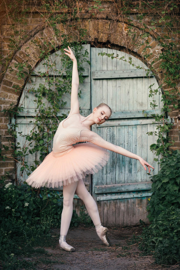 Die Ballerina, die draußen klassisches Ballett tanzt, wirft im städtischen backgro auf stockfoto
