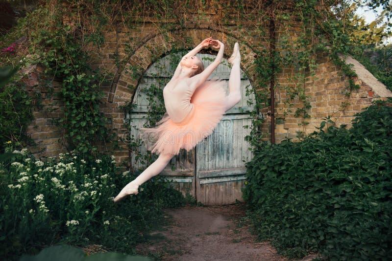 Die Ballerina, die draußen klassisches Ballett tanzt, wirft im städtischen backgro auf stockbilder