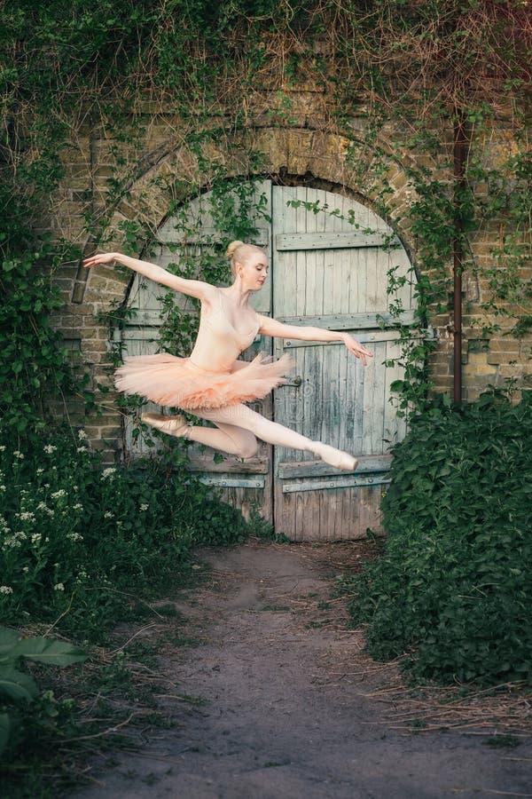 Die Ballerina, die draußen klassisches Ballett tanzt, wirft im städtischen backgro auf stockfotografie