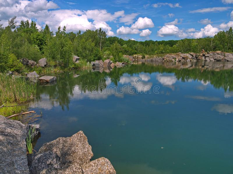 Die Banken des Sees werden mit großen Steinblöcken gezeichnet, in denen die weißen Wolken über den blauen Himmel nachgedacht werd stockbild