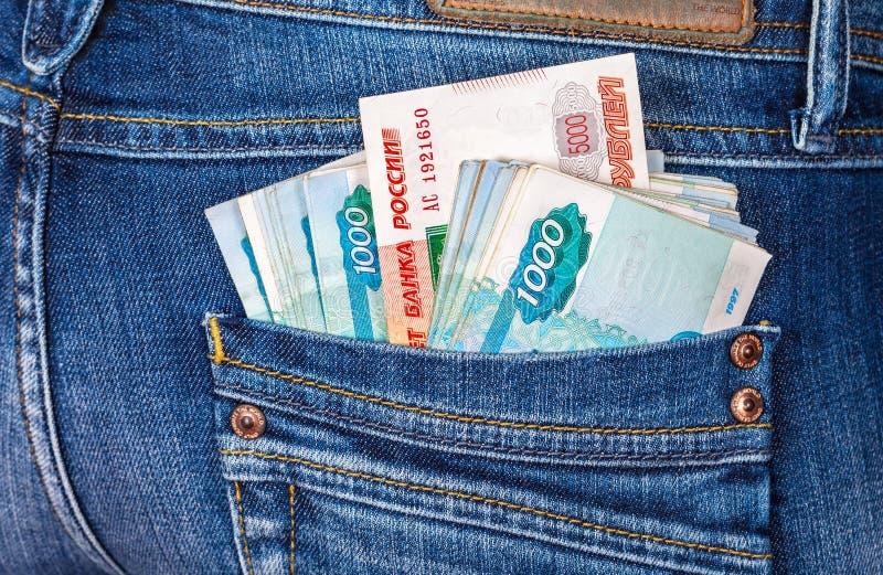 Die Banknoten des russischen Rubels, die aus den hinteren Jeans heraus haften, stecken ein stockbilder