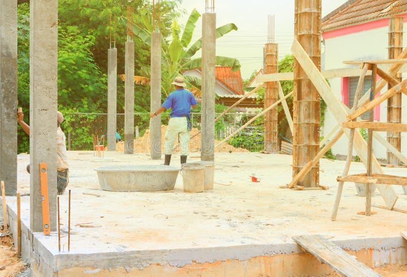 Die Bauarbeiter, die an dem Installationsverschalungsarbeitsplatz zusammenarbeiten, bauen ein Haus lizenzfreie stockbilder