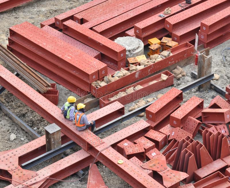 Die Bauarbeiter, die Schutzhelm und Uniform tragen, sitzen auf einem großen roten Baustahl, der etwas Pause macht lizenzfreies stockfoto