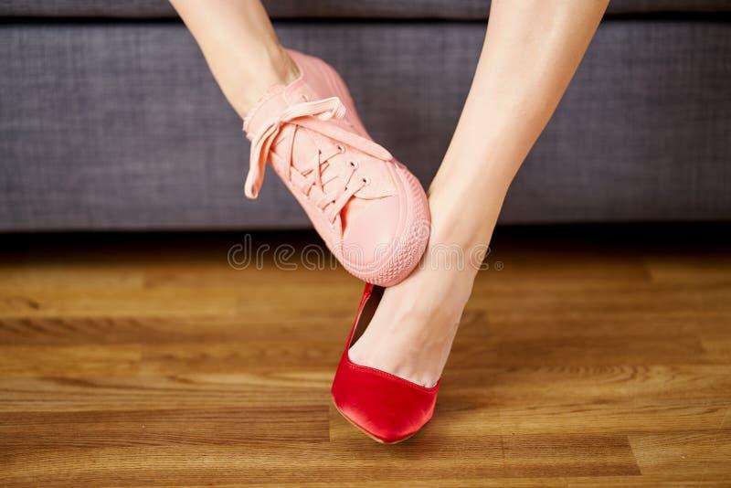 Die Beine der Frau in zwei verschiedenen Schuhen mit roten hohen Absätzen und korallenroten Turnschuhen auf grauem Couchhintergru stockbilder