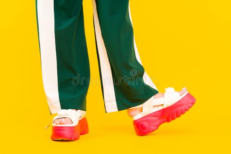 Die Beine der Frauen in den Sportsandalen mit roten Sohlen und in den grünen Hosen mit Streifen stockfotos
