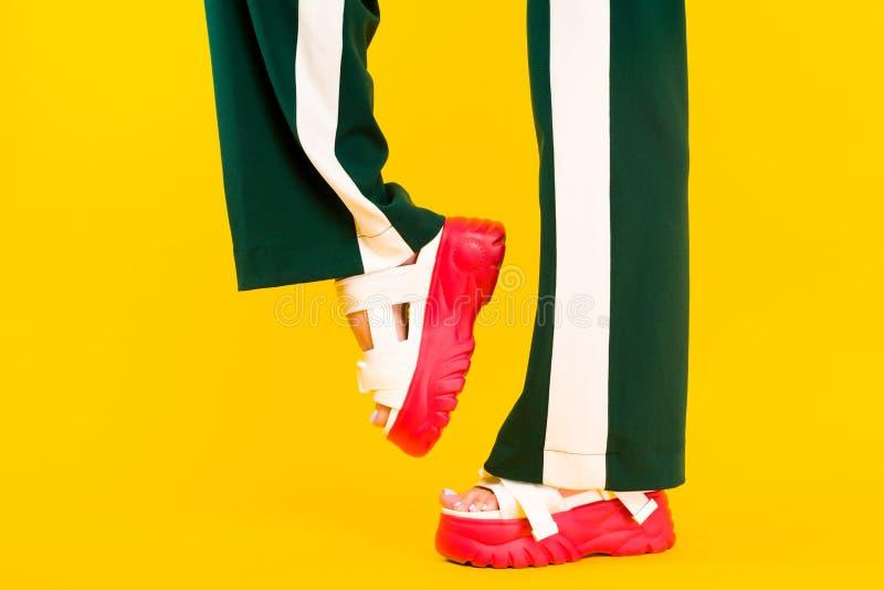 Die Beine der Frauen in den Sportsandalen mit roten Sohlen und in den grünen Hosen mit Streifen lizenzfreie stockbilder