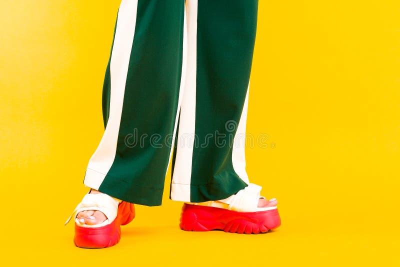 Die Beine der Frauen in den Sportsandalen mit roten Sohlen und in den grünen Hosen mit Streifen lizenzfreies stockfoto