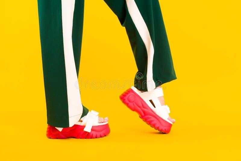 Die Beine der Frauen in den Sportsandalen mit roten Sohlen und in den grünen Hosen mit Streifen lizenzfreie stockfotos