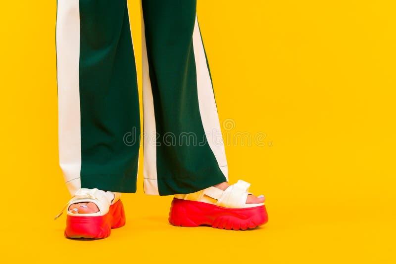 Die Beine der Frauen in den Sportsandalen mit roten Sohlen und in den grünen Hosen mit Streifen stockfotografie