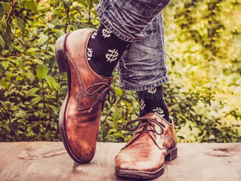 Die Beine der Männer in den stilvollen Schuhen, schwarze Socken mit Mustern stockfotos