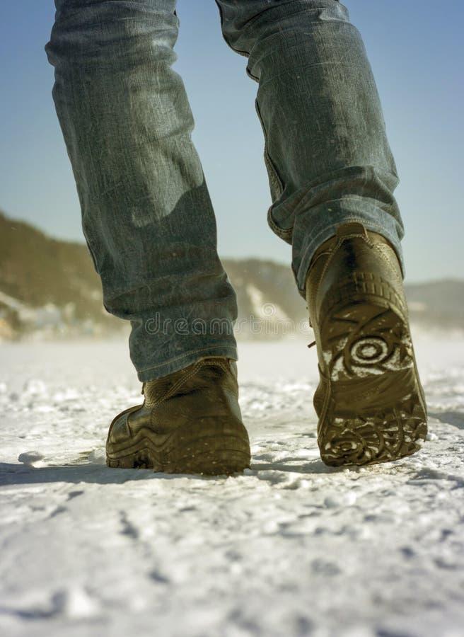 Die Beine der Männer sehen von unterhalb, Winterweg, Reisekonzept an lizenzfreie stockfotografie