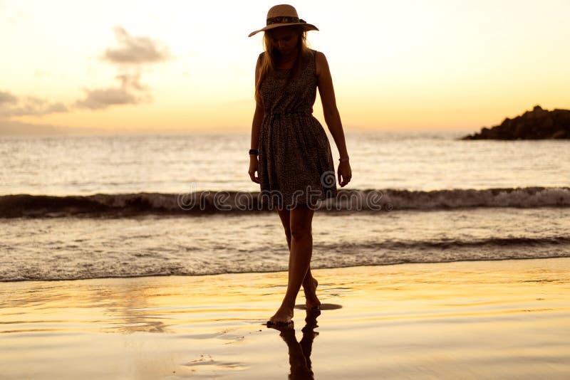 Die Beine des Mädchens bei Sonnenuntergang auf dem Strand stockbild