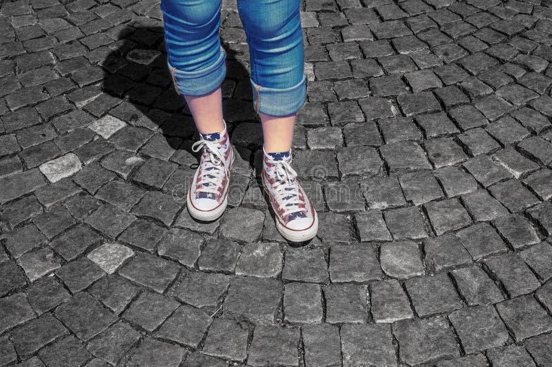 Die Beine des Mädchens in den Gummiüberschuhen auf Pflasterung lizenzfreie stockbilder