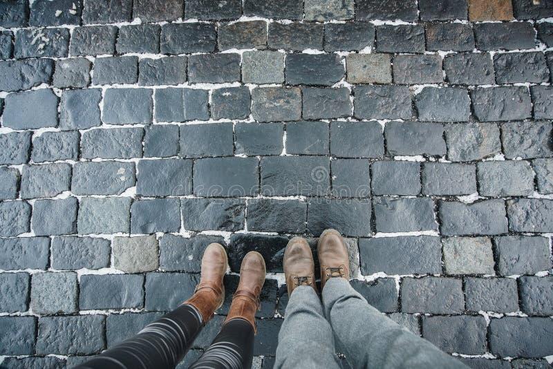Die Beine eines Mannes und der Frau gegen einen Pflasterstein ausgebreitet von einem Stein auf einem roten Quadrat in Moskau, Rus stockfotografie