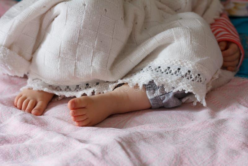Die Beine eines schlafenden kleinen Mädchens mit einen Jährigen lizenzfreies stockbild