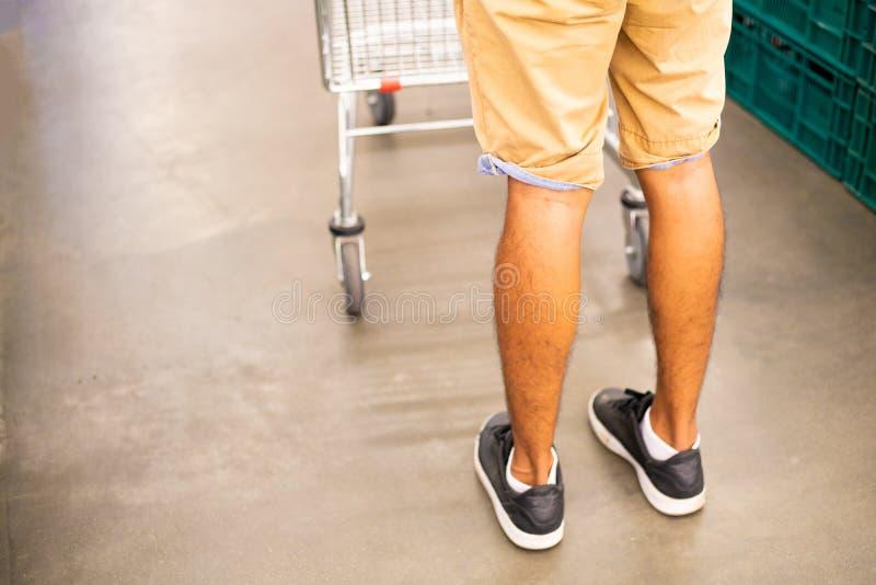 Die Beine und die Laufkatze der Männer Mann wählt Produkte Laufkatze im Supermarkt Innenraum eines Supermarktes, ein leeres stockfotografie